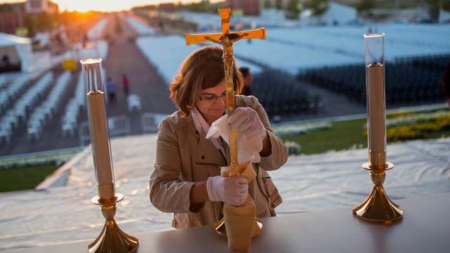 Eine Frau stellt ein Kreuz auf den Altar.