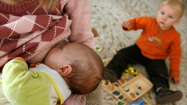 Eine Frau stillt ein Baby, dahinter sitzt ein Kleinkind auf dem Boden.