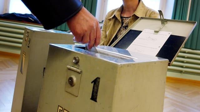 In maun che bitta il scrit da votar en l'urna.