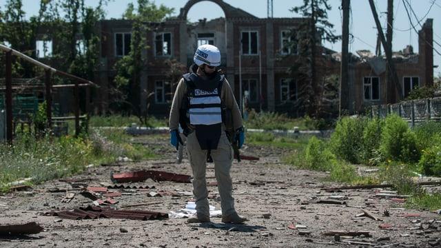 OSZE-Beobachter vor einem zerstörten Gebäude.