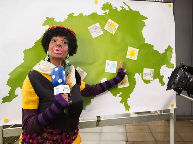 Frau Mgubi als Wetterfee vor Wetterkarte