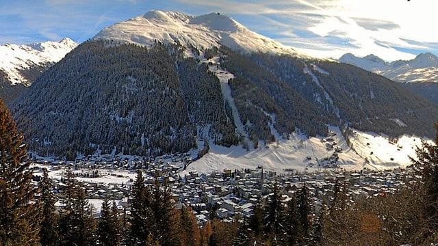 Das Jakobshorn ist durch den Schnee weiss, nur die Tannenwälder erscheinen grün-schwarz. Im Tal liegt in weisser Pracht Davos.