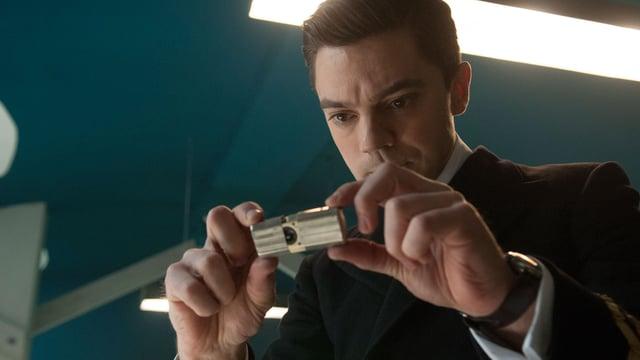 Ein Mann in Uniform fotografiert mit einem kleinen Gerät in der Hand.