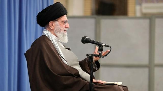 Chamenei mit schwarzem Turban sitzt vor einem  Mikrofon.