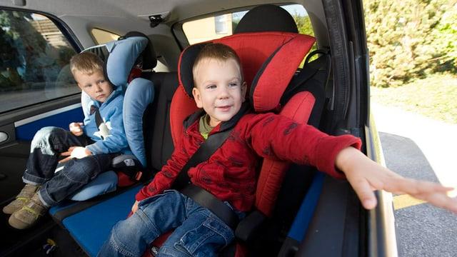 Zwei kleine Buben auf dem Rücksitz eines Autos, angeschnallt in einem roten und einem blauen Kindersitz.
