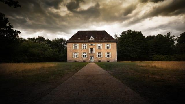 Einsames, verlassenes Haus mit dunklen Wolken am Himmel