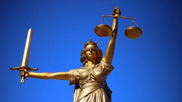 Purtret da la justicia che porta in bindel sur ils egls, ina spada en in maun ed ina stadera en l'auter.