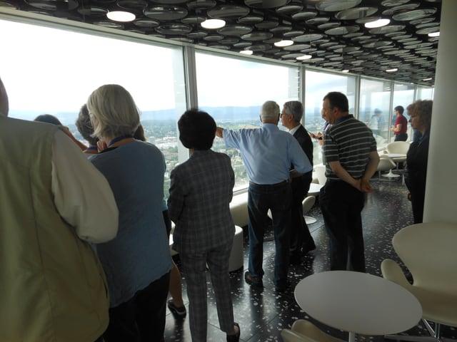 Eine Gruppe Besucher blicken aus dem 38. Stockwerk des Roche-Turms auf Basel hinunter.
