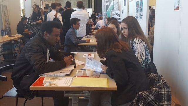 Jugendliche sitzen an einem Tisch und unterhalten sich.