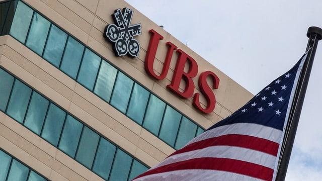 Logo der UBS an einem Gebäude – davor ist ein Ausschnitt der US-Fahne zu sehen