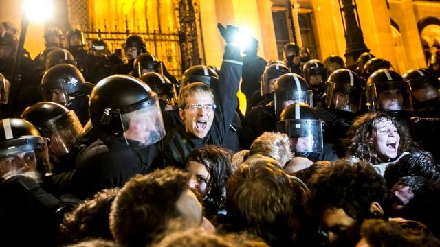 Demonstranten und Polizisten in den Strassen von Budapest.
