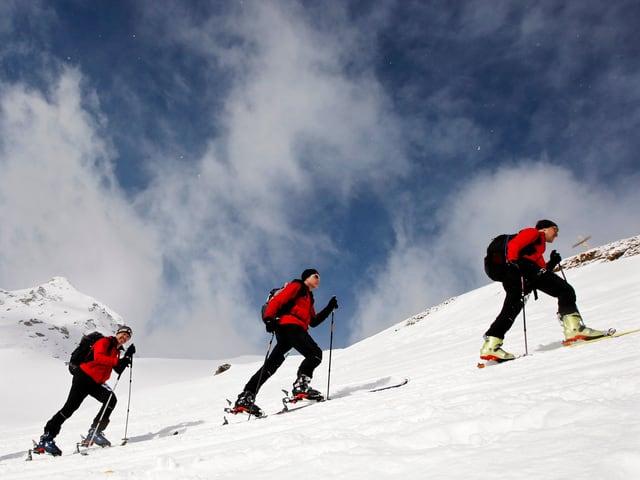 Drei Skitourenläufer sind im Aufstieg. Am Himmel ziehen Wolken auf.