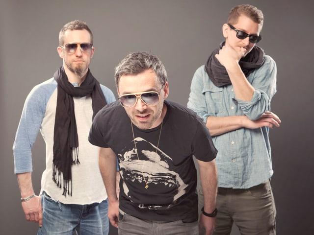 Drei Männer, alle mit Sonnenbrille, stehen vor grauem Hintergrund.