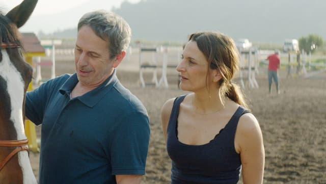 Ein Mann und eine Frau stehen auf einem Trainingsplatz für Pferde.