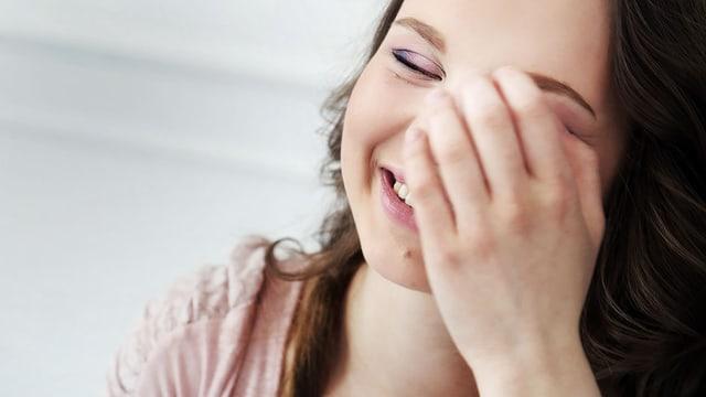 Eine junge Frau lacht mit geschlossenen Augen und greift sich dabei mit der Hand ins Gesicht.
