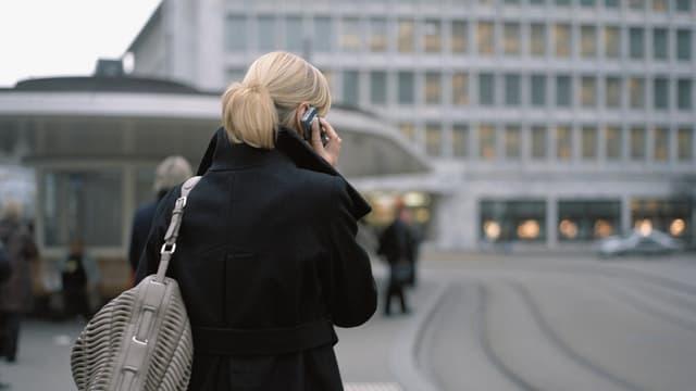 Frau am Handy am Paradeplatz in Zürich