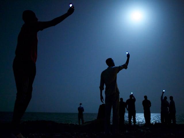 Menschen halten nachts ihr Handy in die Luft.