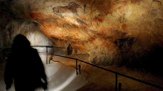 Schatten geht der Höhlenwand entlang, Malereien auf dem Fels.