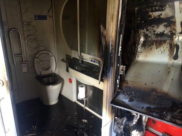 Brandspuren in einer S-Bahn, im Hintergrund ist eine Toilette erkennbar.