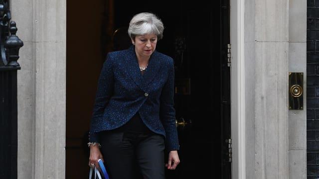 Theresa May vor einem Hauseingang.