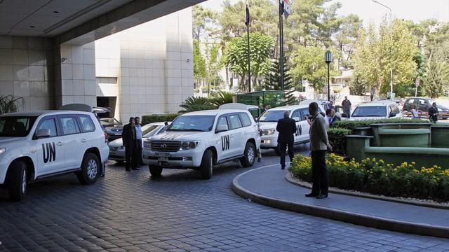 Wagenkolonne der UNO vor Gebäude.