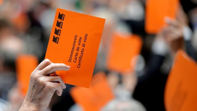 Eine Hand hält an der Versammlung der CVP eine orange Wahlkarte in die Höhe.