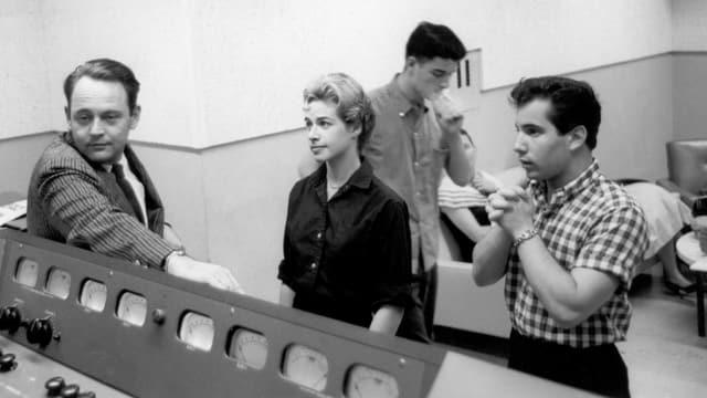 Carole King, Paul Simon (rechts) und Gerry Goffin (hinten) stehen in einem Aufnahme-Studio.