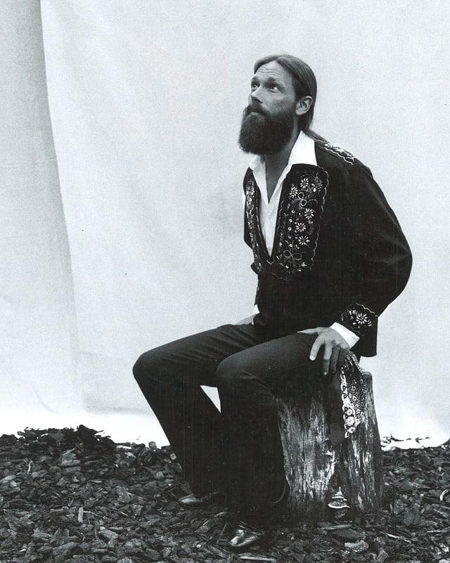Auf Baumstrunk sitzend. schwarzweiss Foto. Am Boden Sägespähne.