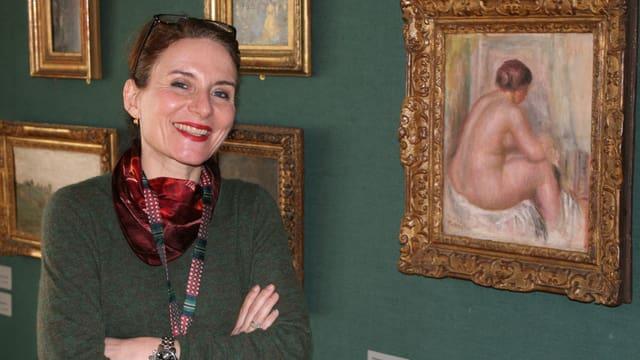 Direktorin Sarah Zürcher vor einer Wand mit Bildern