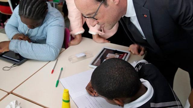 Der Präsident biegt sich über enien Jungen, der in ein Heft schreibt.