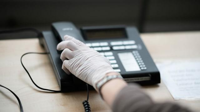 Frauenhand mit Handschuh greift zum Telefonhörer.