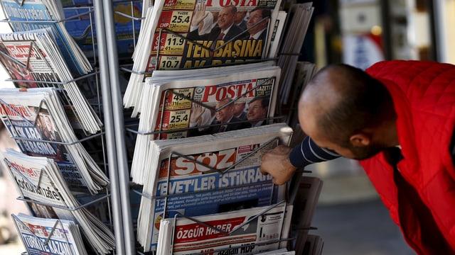 Zeitungen an einem Kisok in der Türkei, ein Mann beugt sich zu einem Exemplar hinunter.