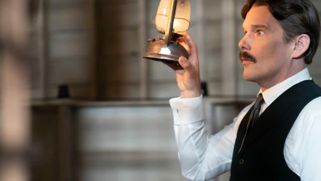 ein Mann hält eine Lampe hoch