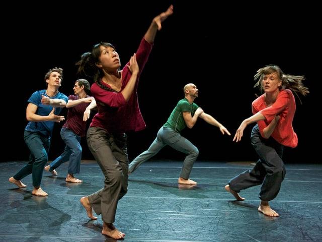 Fünf Tänzerinnen und Tänzer in farbigen Shirts bewegen sich über die Bühne.