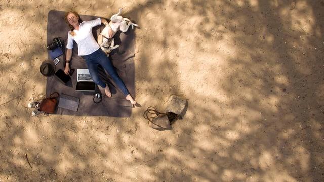 Eine Frau schlummert mit ihrem Hund und Laptop im Schatten eines Baumes.