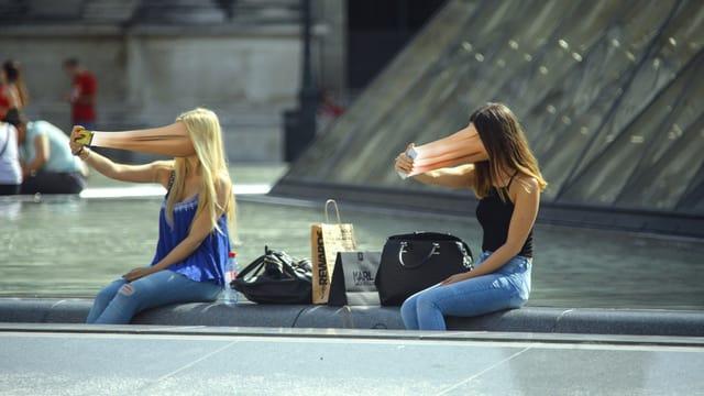 Zwei Frauen mit zum Smartphone hin verzerrtem Gesicht.