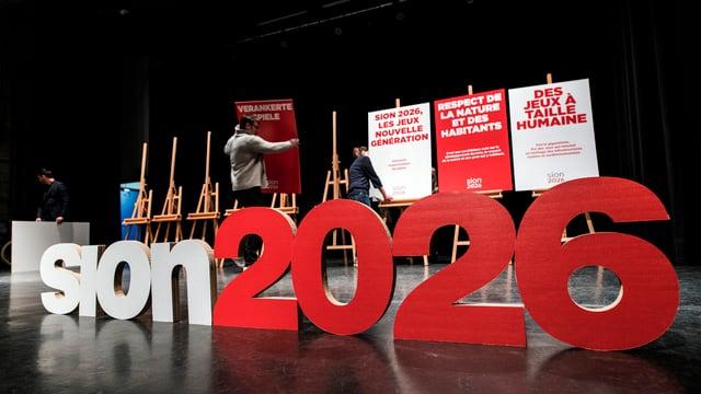 Ein Schriftzug mit Plakaten auf einer Bühne.