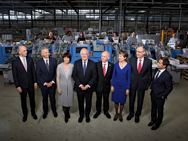 Die sechs Bundesräte und eine Bundesrätin zusammen mit dem Bundeskanzler, sie stehen in einer Druckerei