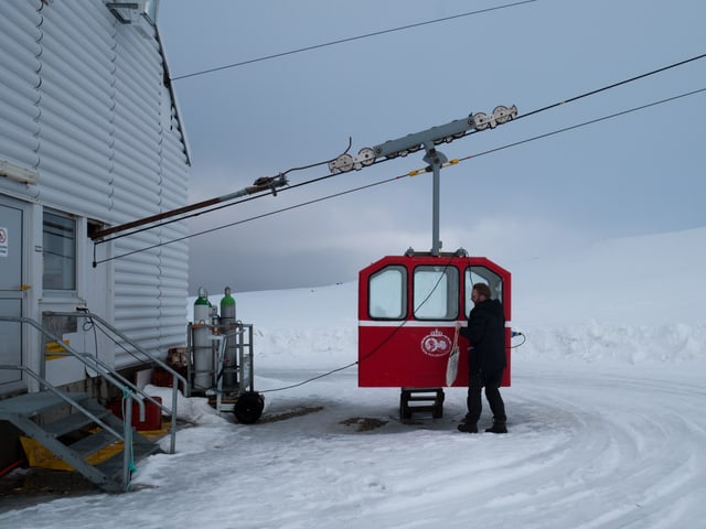 Ein kleine, rote Luftseilbahn-Gondel im Schnee.