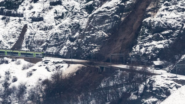 BLS-Bahn auf den Schienen neben einem Erdrutsch.