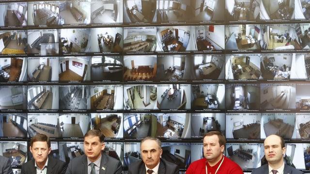 Männer vor Bildschirmen