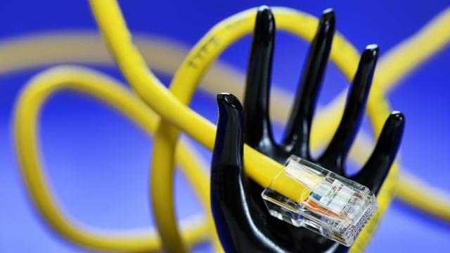 Eine Plastikhand hält ein LAN-Kabel.