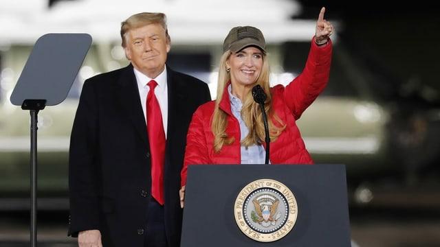 Kelly Loeffler am Rednerpult, hinter ihr steht Donald Trump.