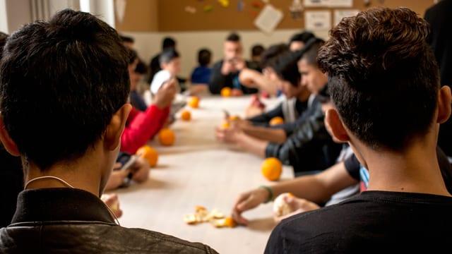 Unbegleitete minderjährige Flüchtlinge sitzen um einen Tisch