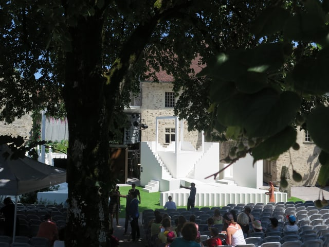 Lindenbaum, darunter Sitze, im Hintergrund Bühne und Schloss