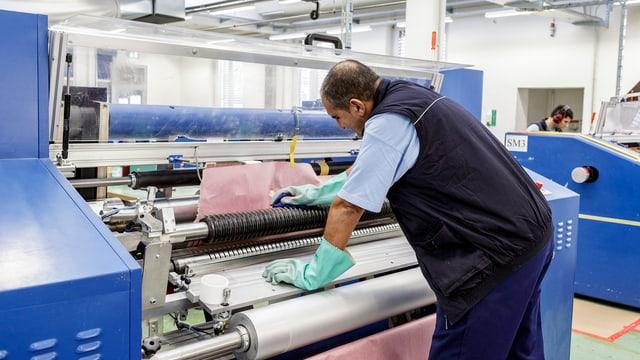 Ein Fabrik-Angestellter an einer Maschine