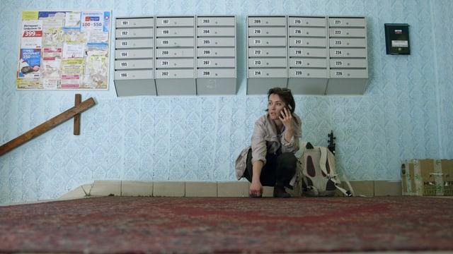Katja Fedulova sitzt in einem russischen Treppenhaus und telefoniert.