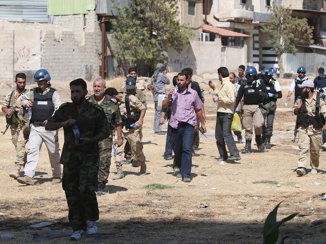 UNO-Inspektoren gehen durch das Viertel Ain Tarma in Damaskus. Sie werden von Kämpfern der Freien Syrischen Armee begleitet. (reuters)