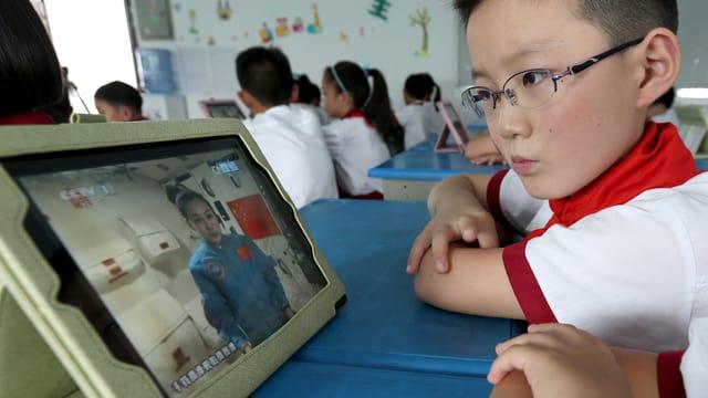 Schüler schaut Vorlesung auf Fernseher.