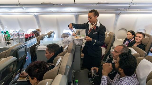 Swiss-Flightattendant serviert Passagieren eine Mahlzeit.